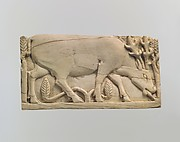 Furniture plaque carved in relief with a stag grazing among plants