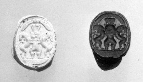 Scarab seal with Bes dominating two lions below a winged sun disc