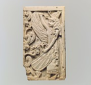 """Furniture plaque carved in relief with a winged female figure and a """"sacred tree"""""""