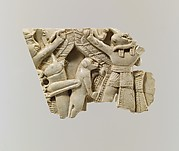 Plaque fragment with a monkey and a locust between a winged figure and ram-headed figures