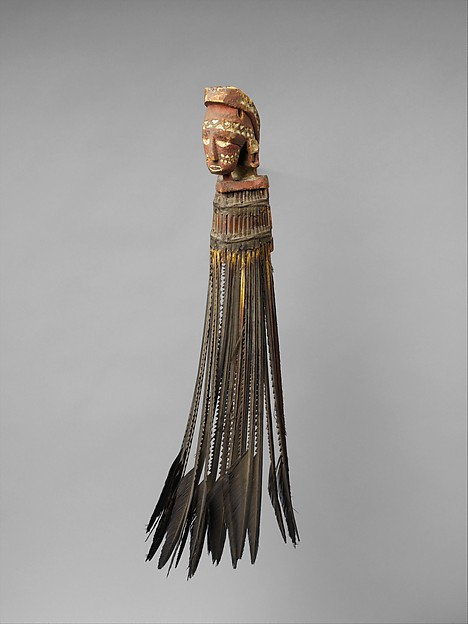 Object: War Charm, Neck Ornament Indigenous name: Unknown Culture/location: Papua New Guinea, Admiralty Islands, Matankor People Date: Late 19th/ Early 20th century Materials: wood, paint, frigate bird feathers, fiber, glass beads, parinarium nut paste Dimensions: 19 3 /4 in Institution and accession number: The Metropolitan Museum, 1980.546