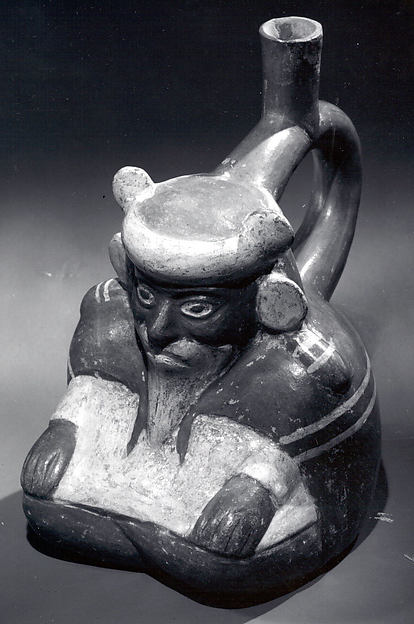 Stirrup spout bottle with sitting figure