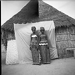 Two Women in Front of a Thatch-Roof House