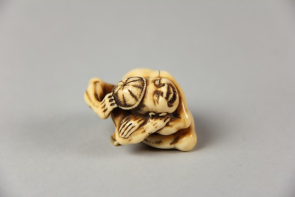 Netsuke of Acrobat Removing his Hat with His Foot