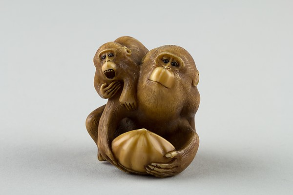 Netsuke of a Female Monkey Holding a Nut while her Baby Crawls on her Back