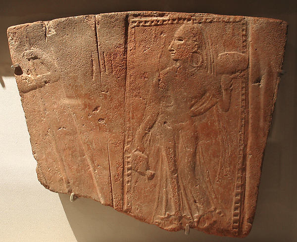 Tile showing a woman carrying a pot