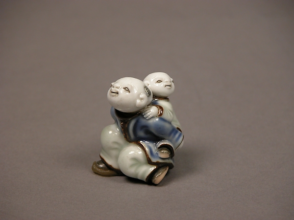 染付子運び唐子形根付<br/>Child Carrying an Infant Netsuke