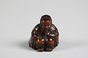 Netsuke of Seated Figure of an Old Man with Backpack Containing a Mask