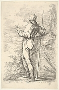 Helmeted man holding a staff next to a rocky wall, shown from behind, from the series 'Figurine'