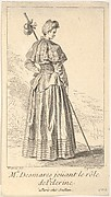 Actress Charlotte Desmares playing the role of a pilgrim, shown from behind with her head turned toward the right, she holds a walking stick, scallop shells adorn her cape