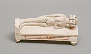 Reclining female figure on a bed