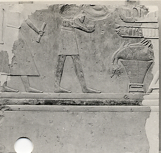 Relief from the tomb of Queen Neferu: a scribe and a cupbearer approach the queen's offering table - see 26.3.353-1