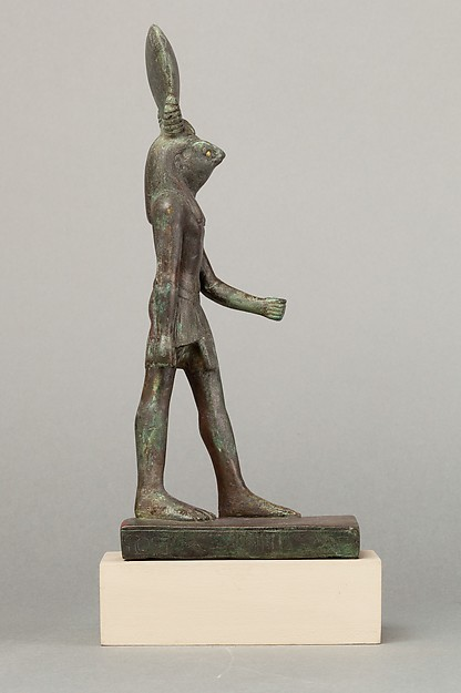 An ancient base asking blessings from Heka for the Scribe of the Library of Atum Pa-kap, son of the Prophet of Atum Pa-iry-kap and the mistress of the House Hr-ib-Wadjet; above the ankles the statuette is brass and therefore modern