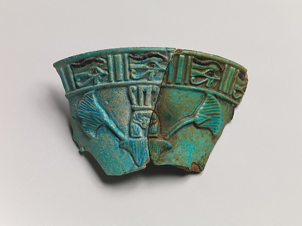 Relief chalice rim fragment with a wedjat frieze and below that a Hathor sistrum head emerging from papyrus plants