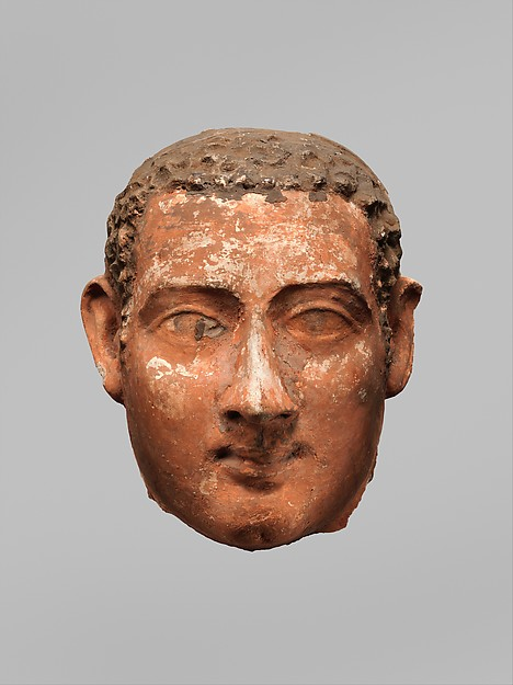 Mask of a man with short curly hair and long sideburns
