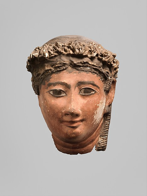 Mask of a woman with corkscrew locks and ball earrings