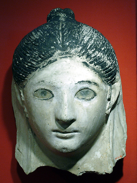 Mask of a woman with her hair in a small knot