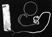 A plaque tied to a bracelet or ring with a cord