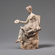 Terracotta statuette of Aphrodite seated on a rock