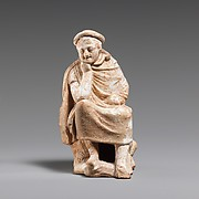 Terracotta statuette of a youth seated on a rock