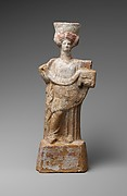 Terracotta statuette of a standing woman with a basket and wreath