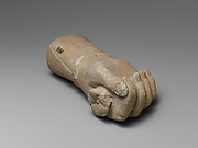 Limestone statue fragment of a right hand with a bracelet, holding a flower