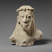 Upper part of a limestone statuette of a male aulos player