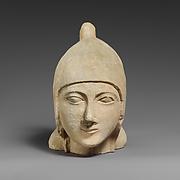 Limestone head of a beardless male wearing a conical helmet