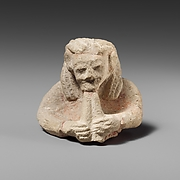 Upper part of a limestone male aulos player