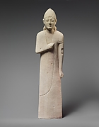 Limestone statuette of a beardless male votary with a conical helmet