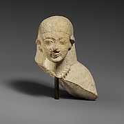 Upper part of a female limestone votary