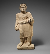 Limestone statuette of a boy with a wreath of leaves