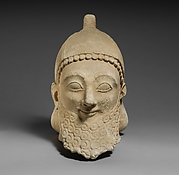 Limestone head of a bearded male wearing a conical helmet