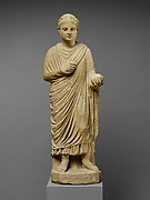 Limestone statue of a wreathed boy holding a ball or piece of fruit