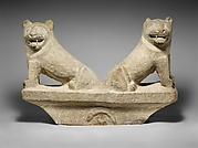 Limestone finial of a funerary stele with two seated lions