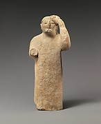 Limestone figure holding a mask