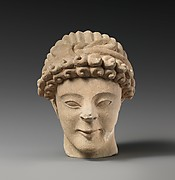 Limestone head of male votary with fillet