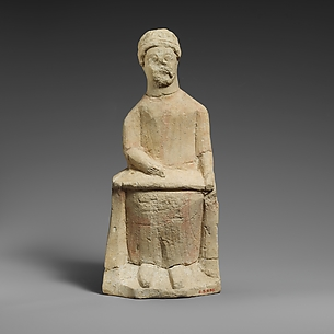 Limestone statuette of a seated beardless male votary writing on a scroll