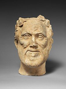 Limestone head of bearded male votary with wreath of leaves