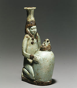 Faience double-spouted vessel in the form of a kneeling woman holding a jar