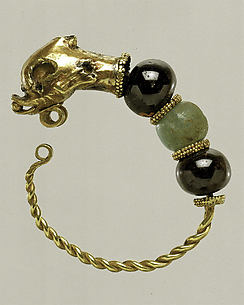 Gold, beryl, and garnet earring with head of a doplhin