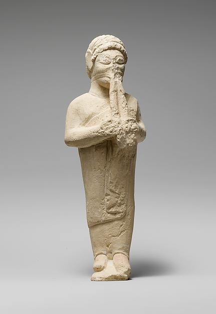 Limestone statuette of a flute-player