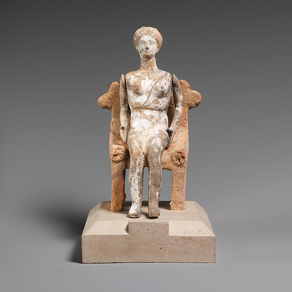 Terracotta doll with articulated arms seated on a chair