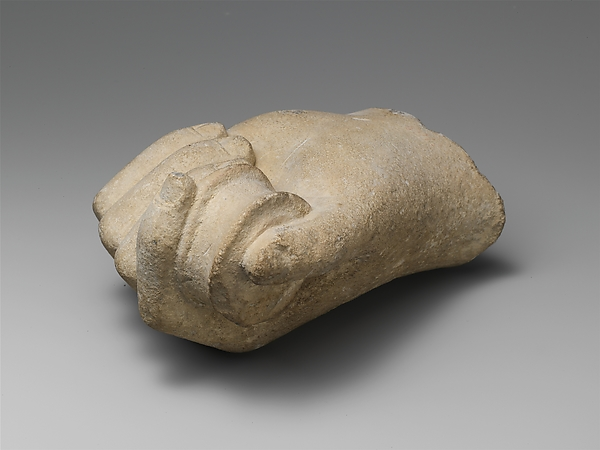 Limestone statue fragment of a hand holding a pyxis or bobbin