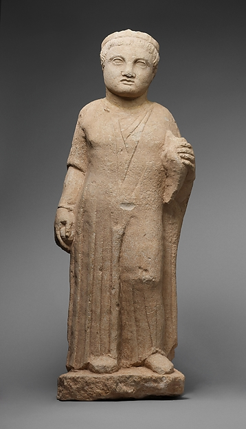 Limestone statue of a male votary holding a dove and an apple