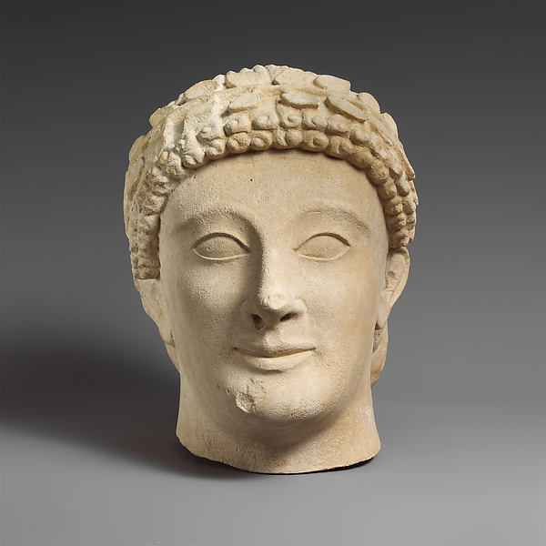 Limestone head of a beardless male votary with a wreath of leaves