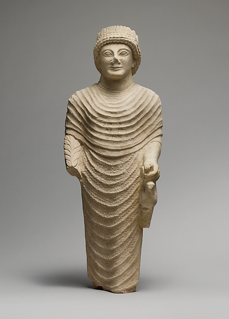 Limestone statue of a male votary holding a bird in the left hand