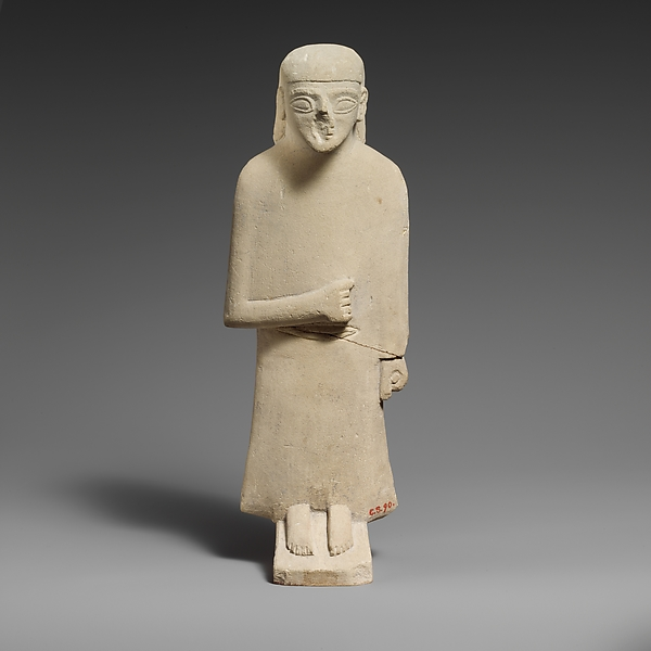 Limestone statuette of a male votary with a long garment and a plain headdress