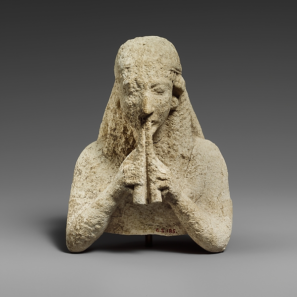 Upper part of a limestone statuette of a female aulos player