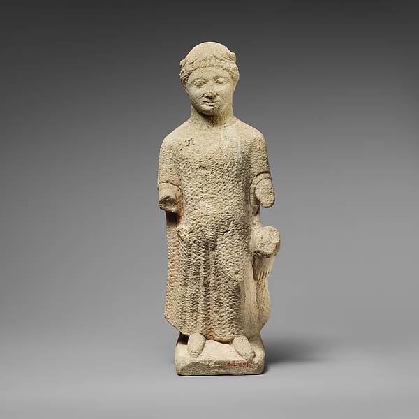 Limestone statuette of a boy holding a bird